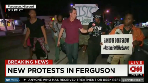 Jake Tapper live reporting in  Ferguson MO, with ISIS sign in background